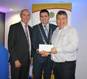 Peter Dineen of Coachford TidyTowns Association receiving his cheque from Mayor of Cork County Cllr. John Paul O' Shea and Tim Lucey, Chief Executive of Cork County Council.