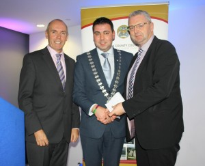 County Mayor O' Shea presenting Tom Butler of Ballincollig Tidy Towns with their cheque of €500 in the presence of Tim Lucey, Chief Executive of Cork County Council